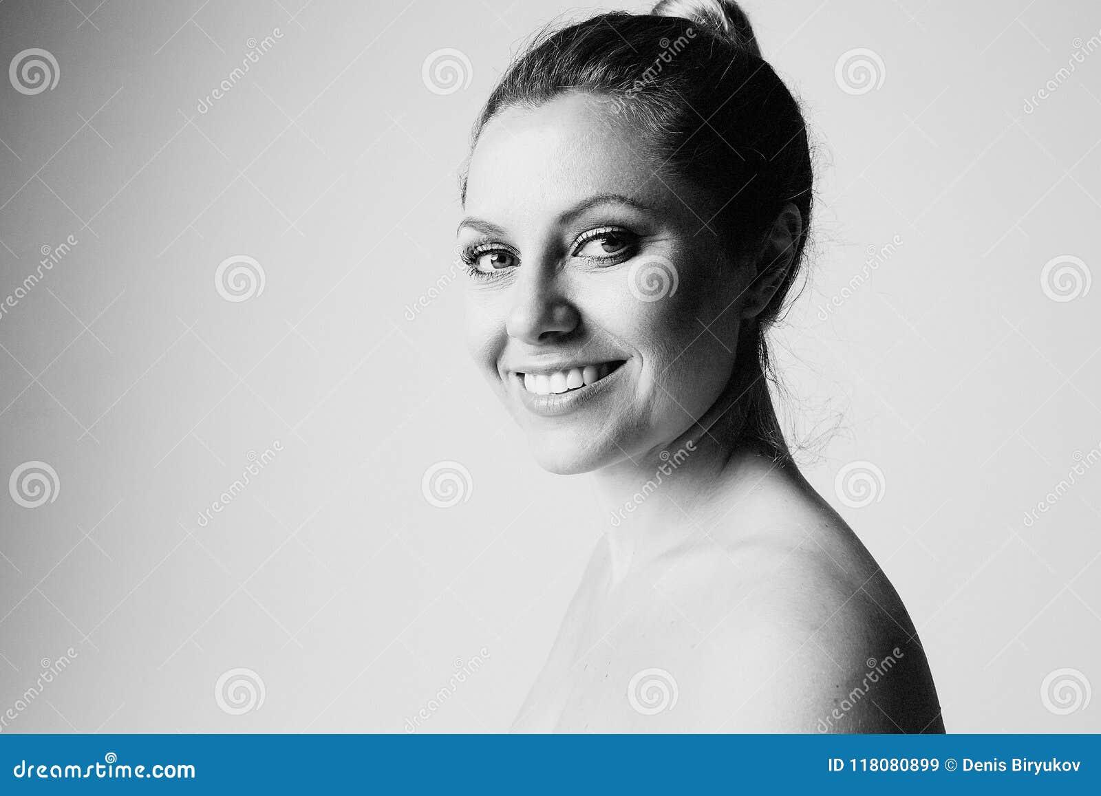 Härlig kvinna med ren hud, naturligt smink och vita tänder på grå studiobakgrund Medicinsk och kosmetisk ansiktsbehandling