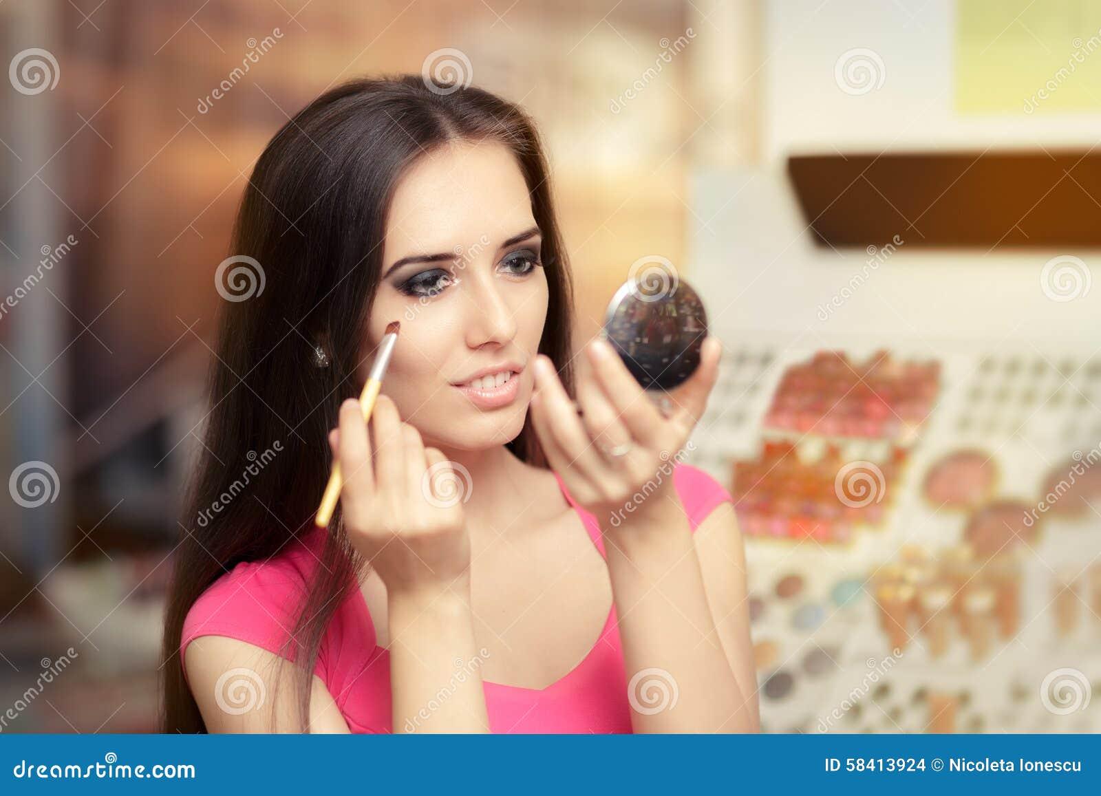 Härlig kvinna med sminkborsten som ser i en spegel