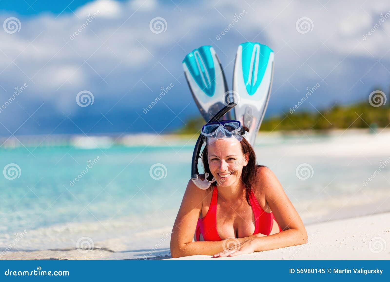Härlig kvinna på den tropiska stranden som tycker om att snorkla
