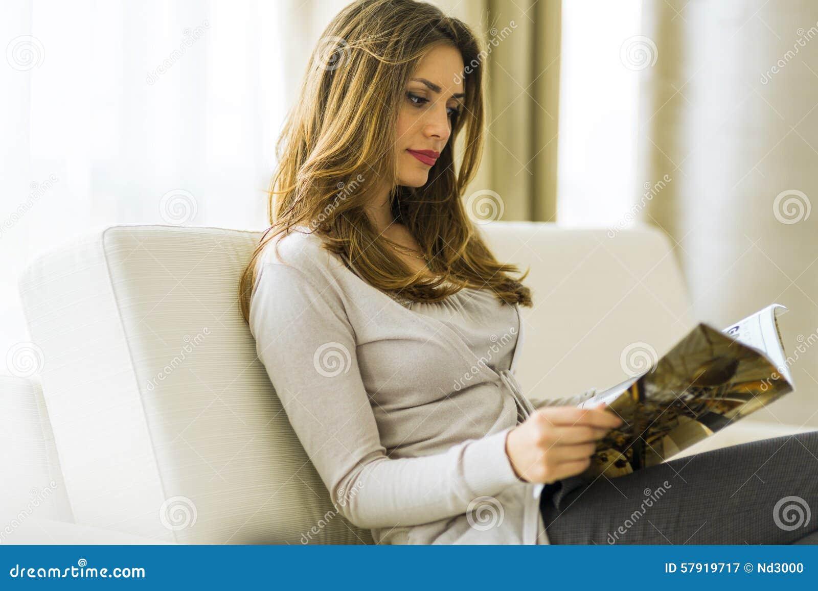 Härlig kvinna på en soffa som läser ett papper i vardagsrummet