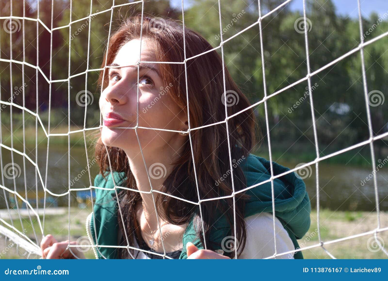Härlig kvinna på stranden som netto poserar med en volleyboll