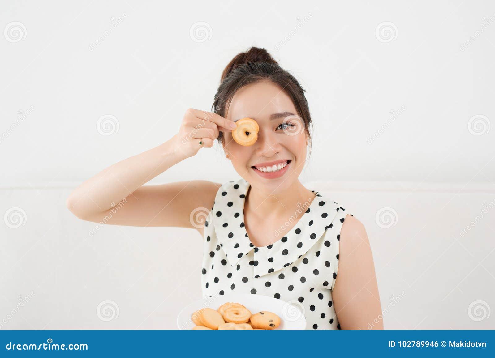 Härlig kvinna som äter kakor som hemma sitter på en soffa