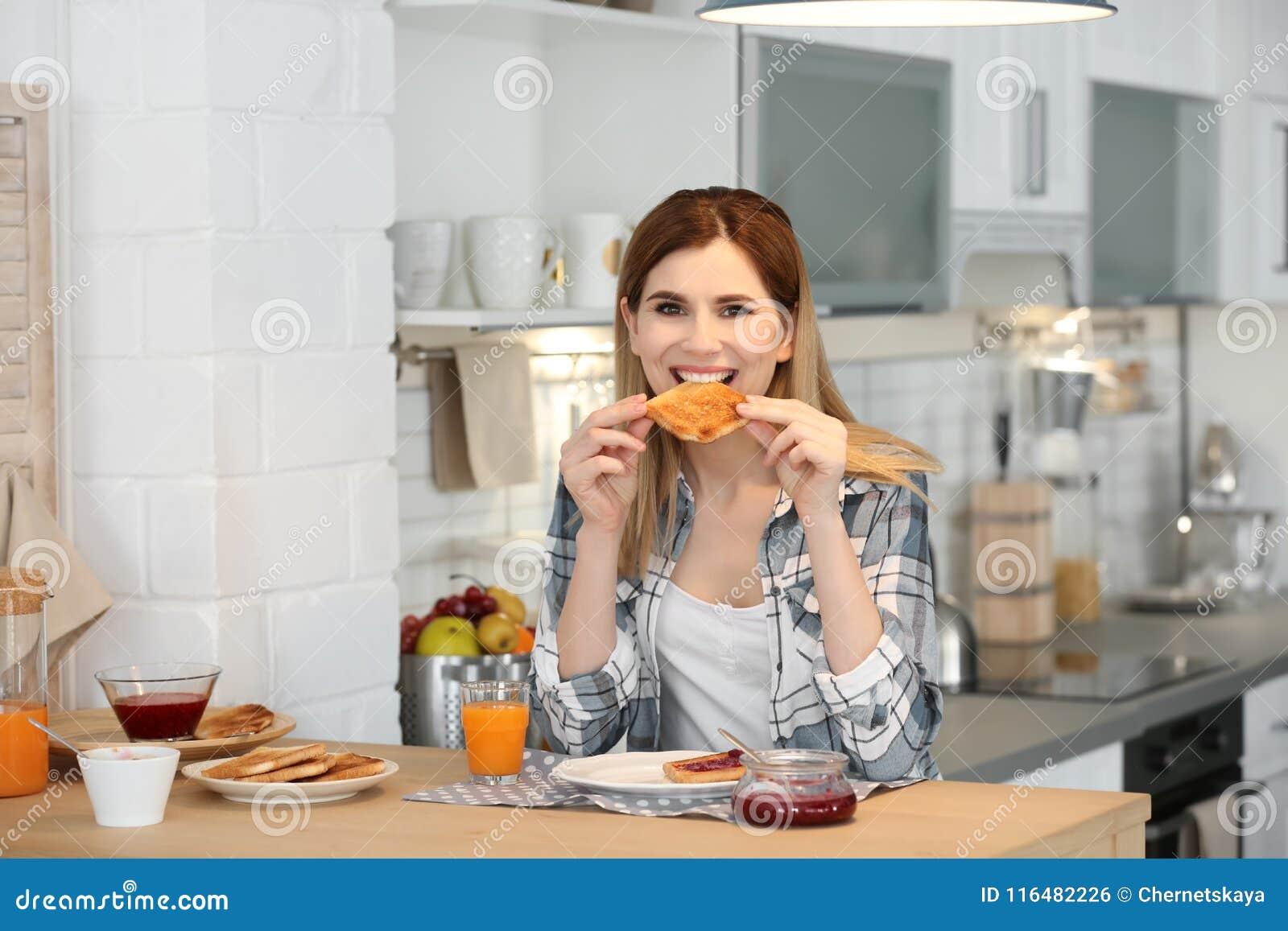 Härlig kvinna som äter smakligt rostat bröd med driftstopp