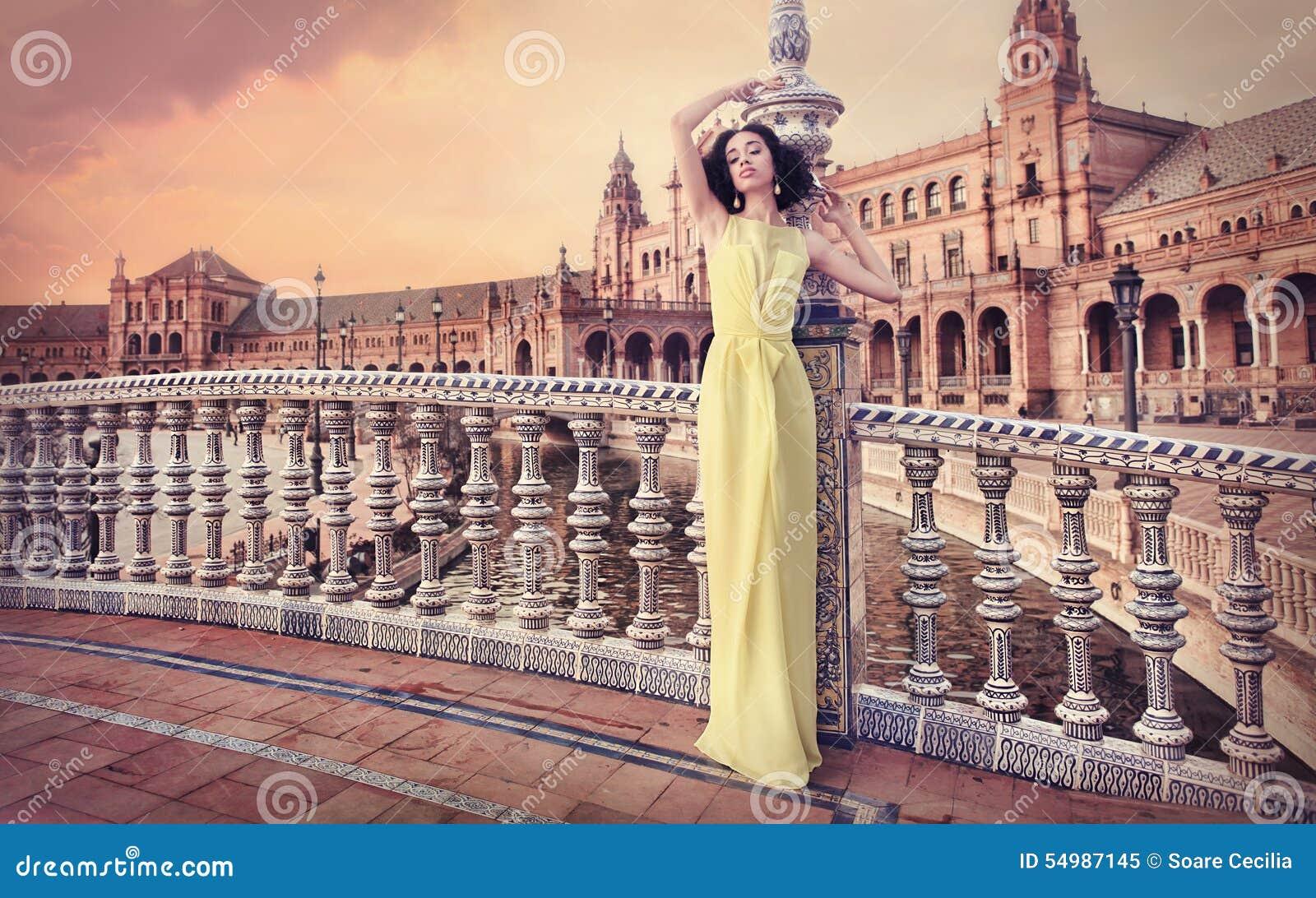Härlig kvinna som bär den långa gula klänningen