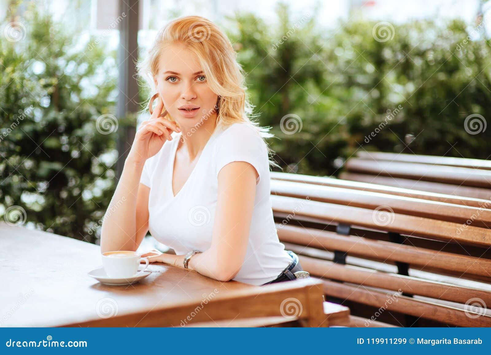 Härlig kvinna som dricker kaffe i ett kafé