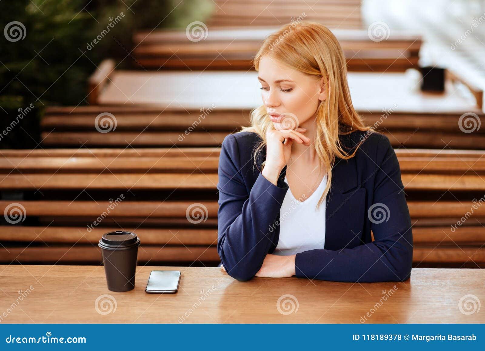 Härlig kvinna som dricker kaffe i ett kafé och en telefon