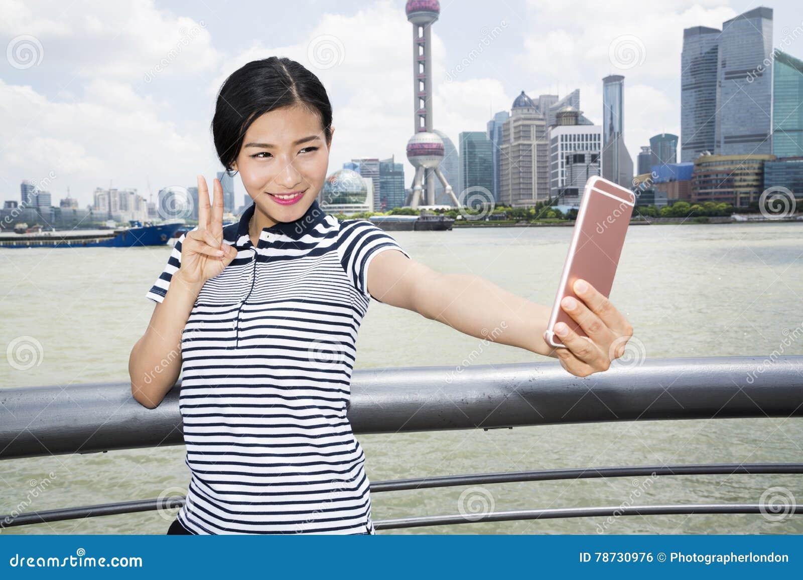 Härlig kvinna som gör en gest fredtecknet, medan ta selfie till och med den smarta telefonen mot Pudong horisont