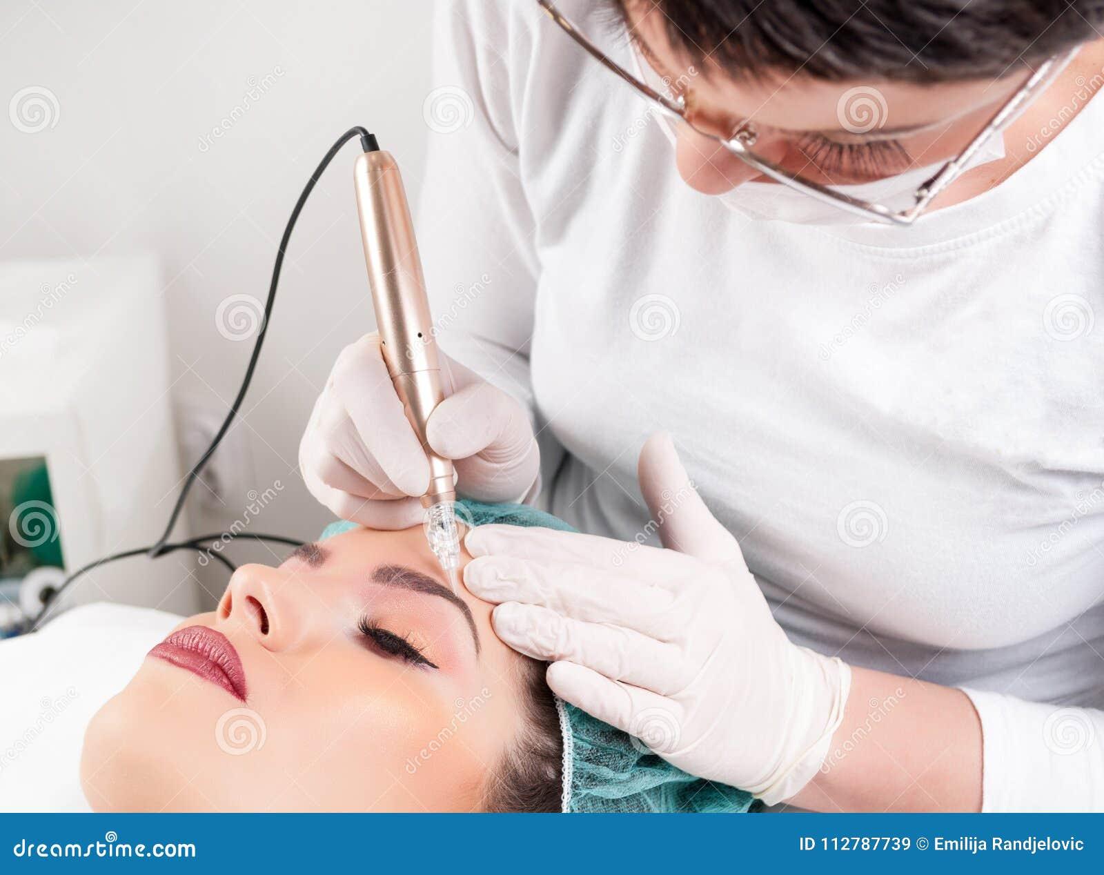 Härlig kvinna som har den yrkesmässiga ögonbryntatueringen