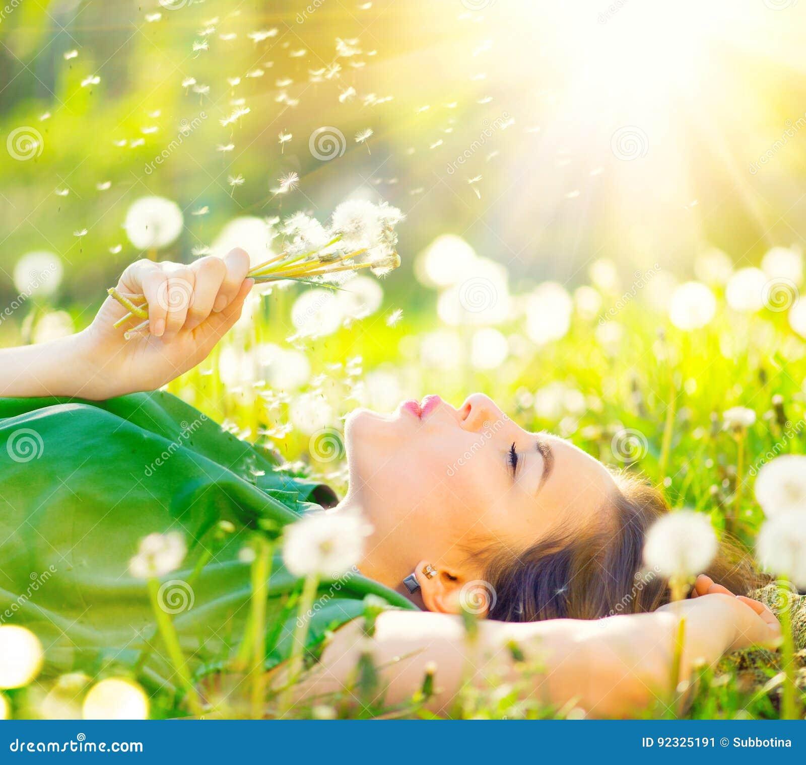 Härlig kvinna som ligger på fältet i grönt gräs och blåser maskrosen
