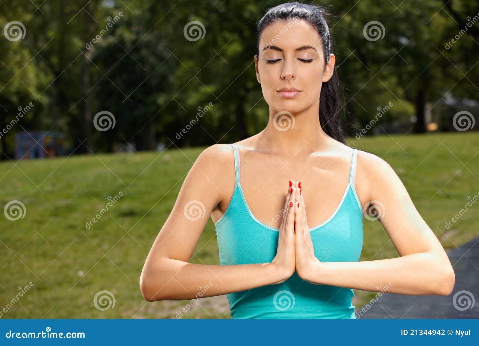 Härlig kvinna som mediterar i park