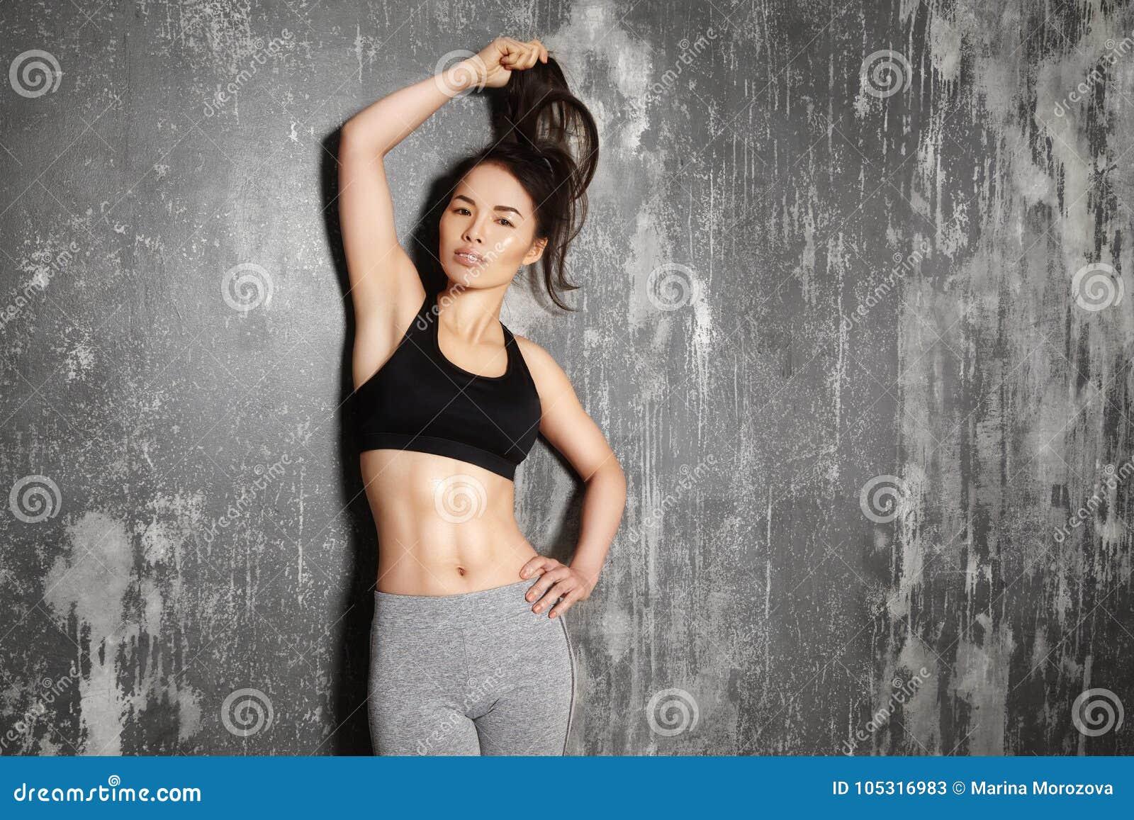 Härlig kvinna som poserar i sportkläder Sinnlig brunettkvinna med perfekta kroppformer Sund livsstil