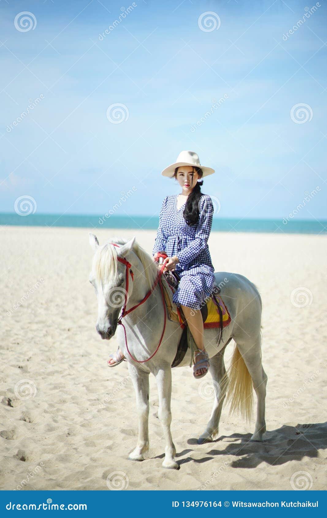 Härlig kvinna som rider en häst på stranden