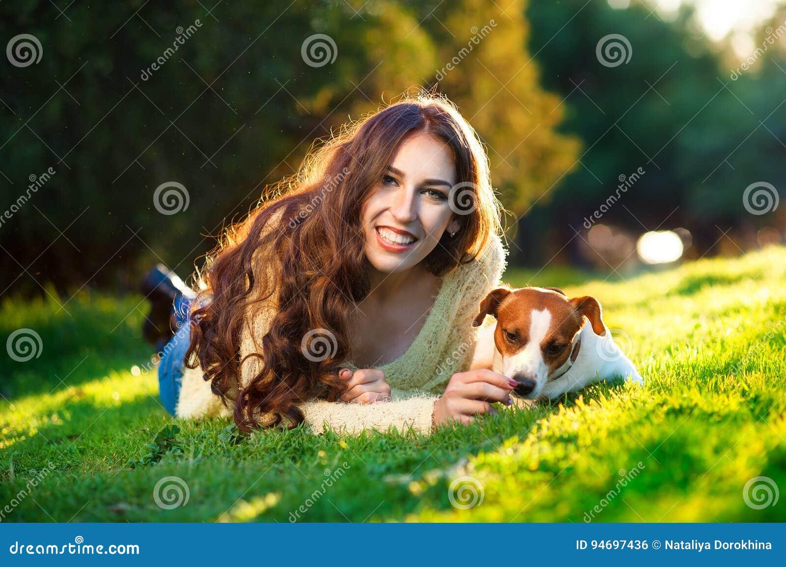 Härlig kvinna som spelar med hennes hund Jack Russell Terrier utomhus- stående serie