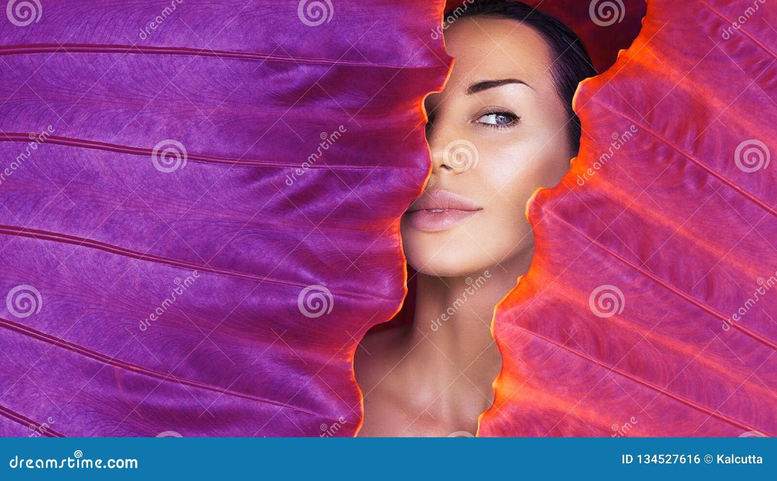 Härlig kvinnaframsida med naturligt näckt smink på en tropisk bladbakgrund sund livstid renhet