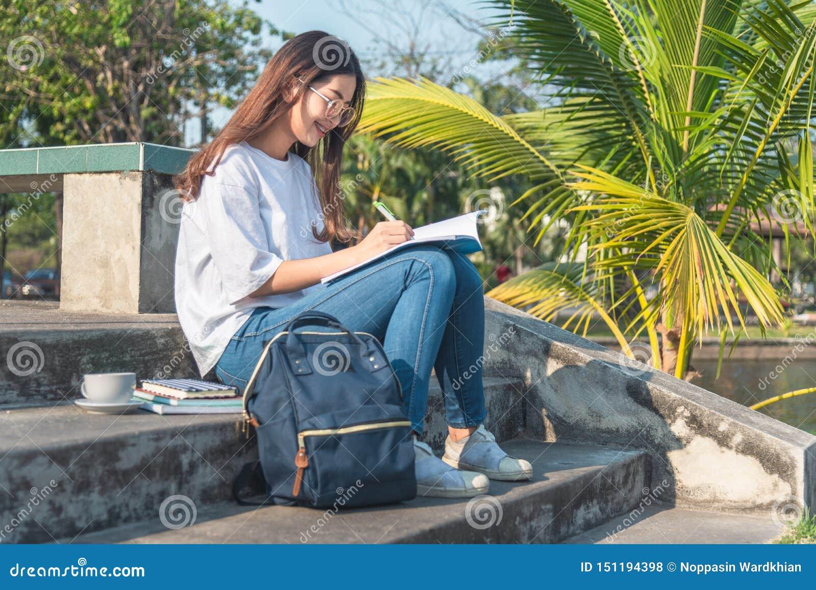 Härlig kvinnahandstil in i hennes dagbok, i parkerar