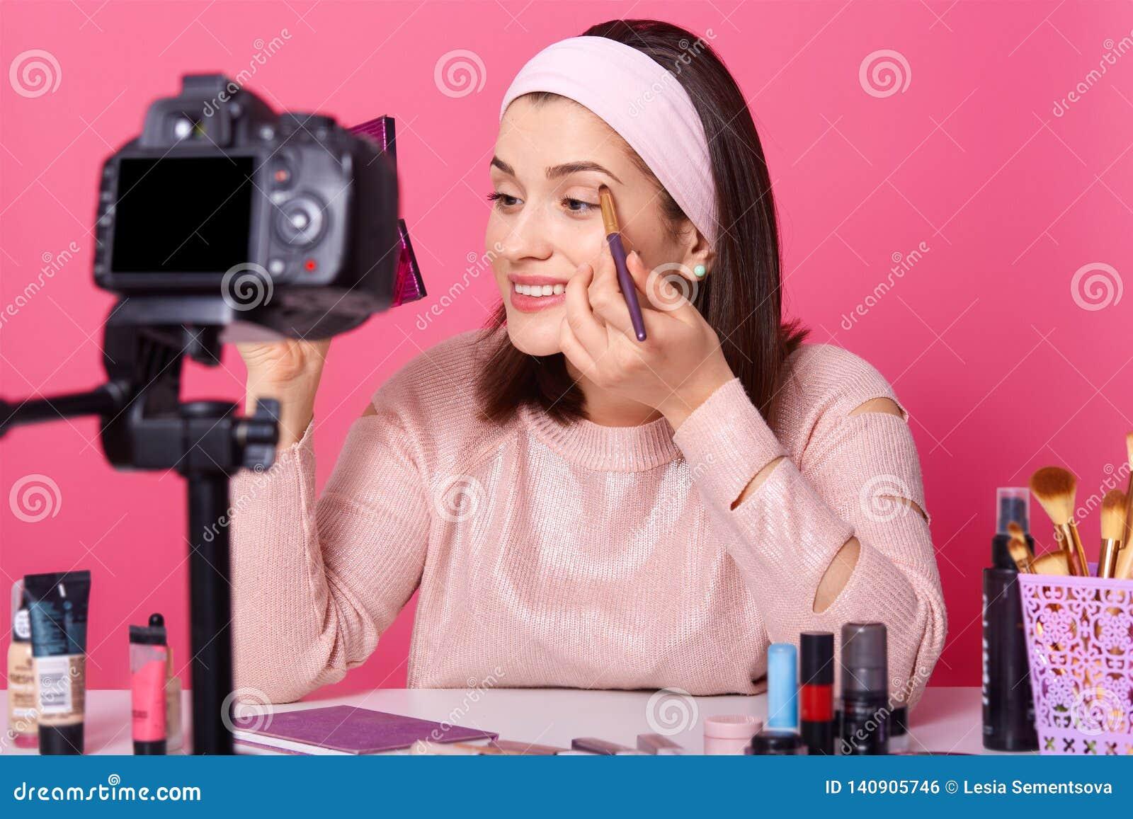 Härlig kvinnlig rekordvideo Den Yong bloggeren visar hur man applicerar ögonskugga Damadvetisesskönhetsmedel på hennes kanal Kvin