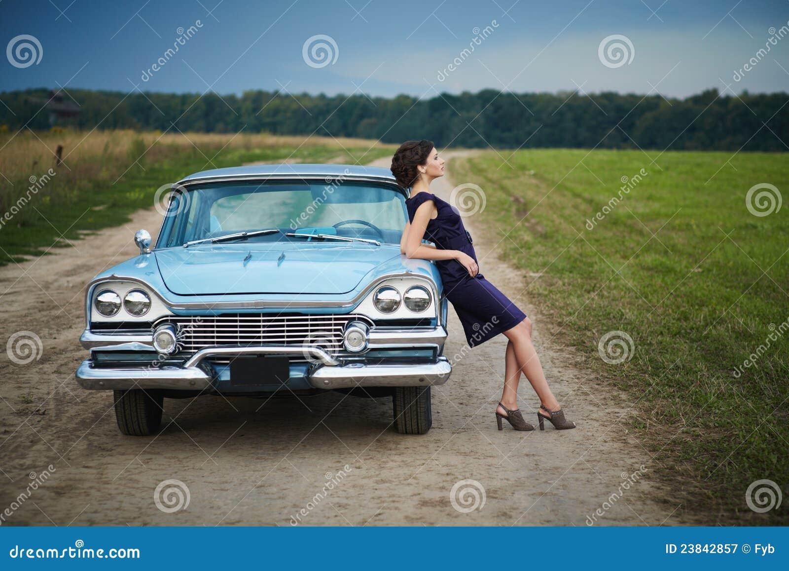 Härlig lady som plattforer nära den retro bilen