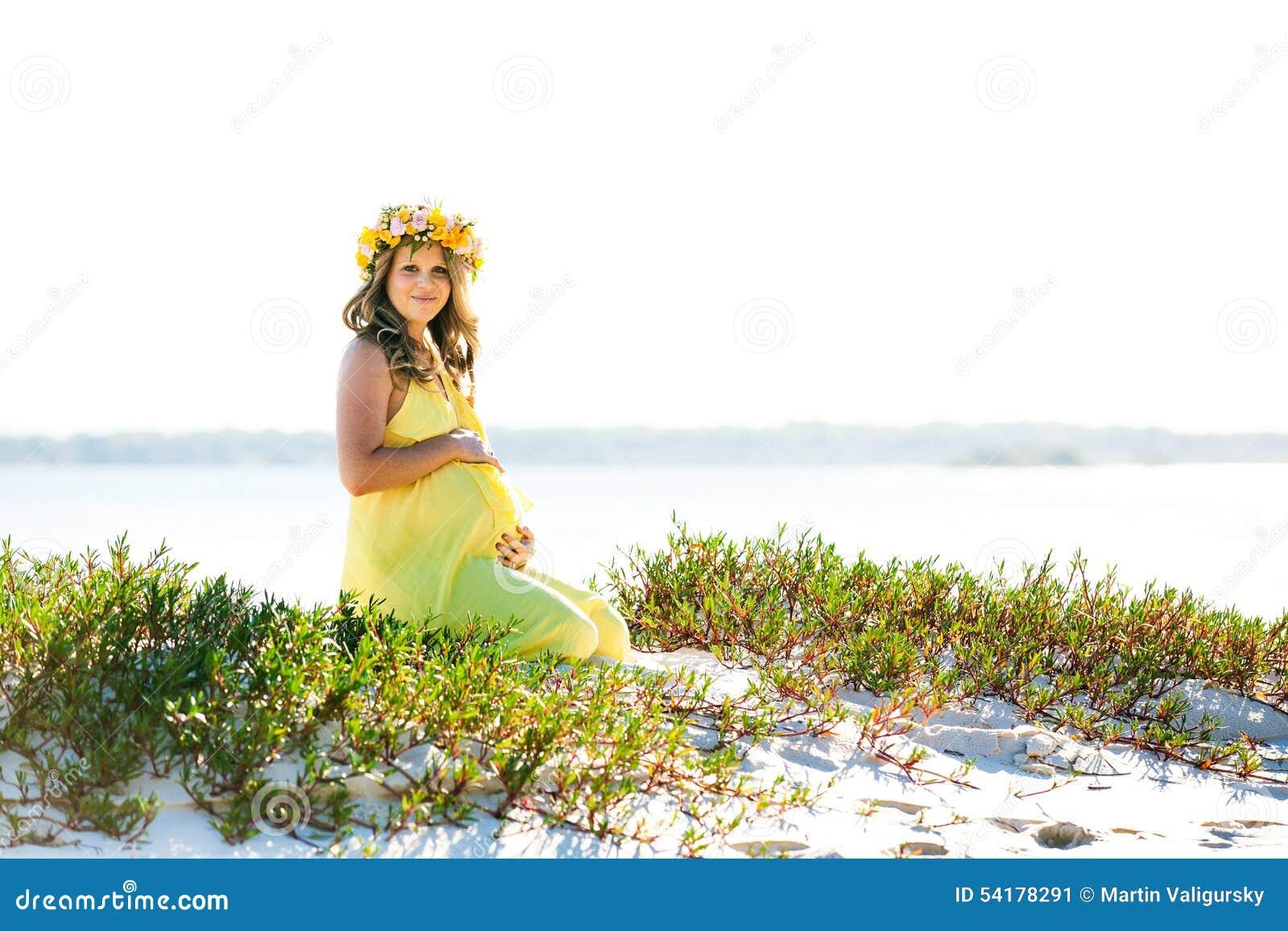 Härlig le gravid kvinna med blommor som sitter på en strand