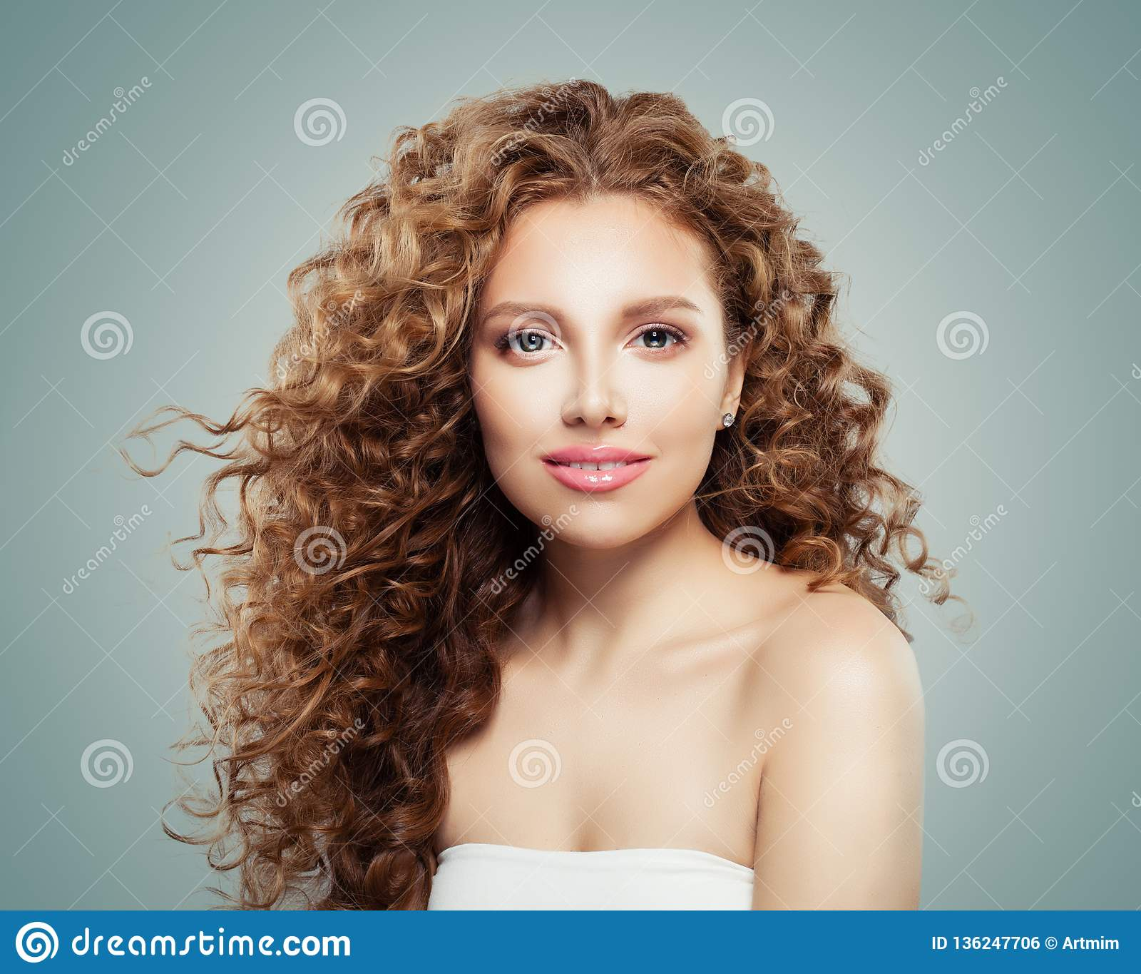 Härlig le kvinna med sunt lockigt hår på grå bakgrund Rödhårig manflicka