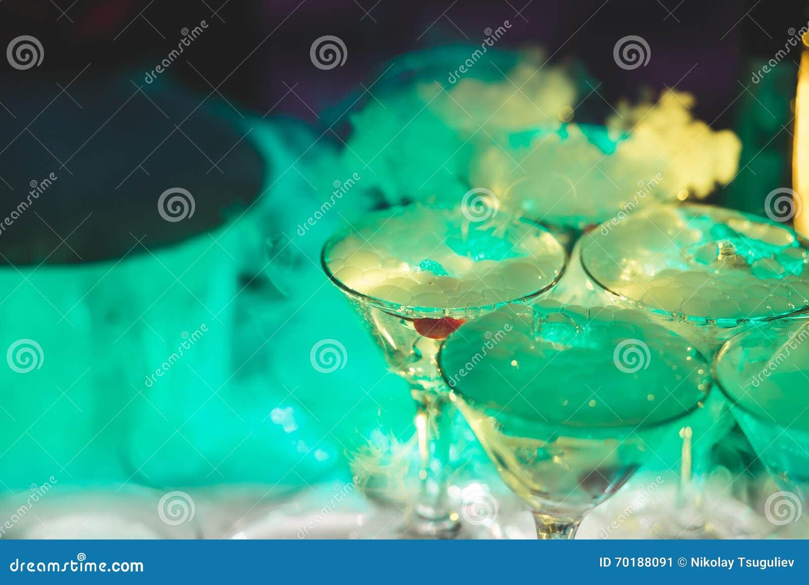 Härlig linje av olika kulöra alkoholcoctailar med rök på ett julparti, en tequila, en martini, en vodka och andra på delen