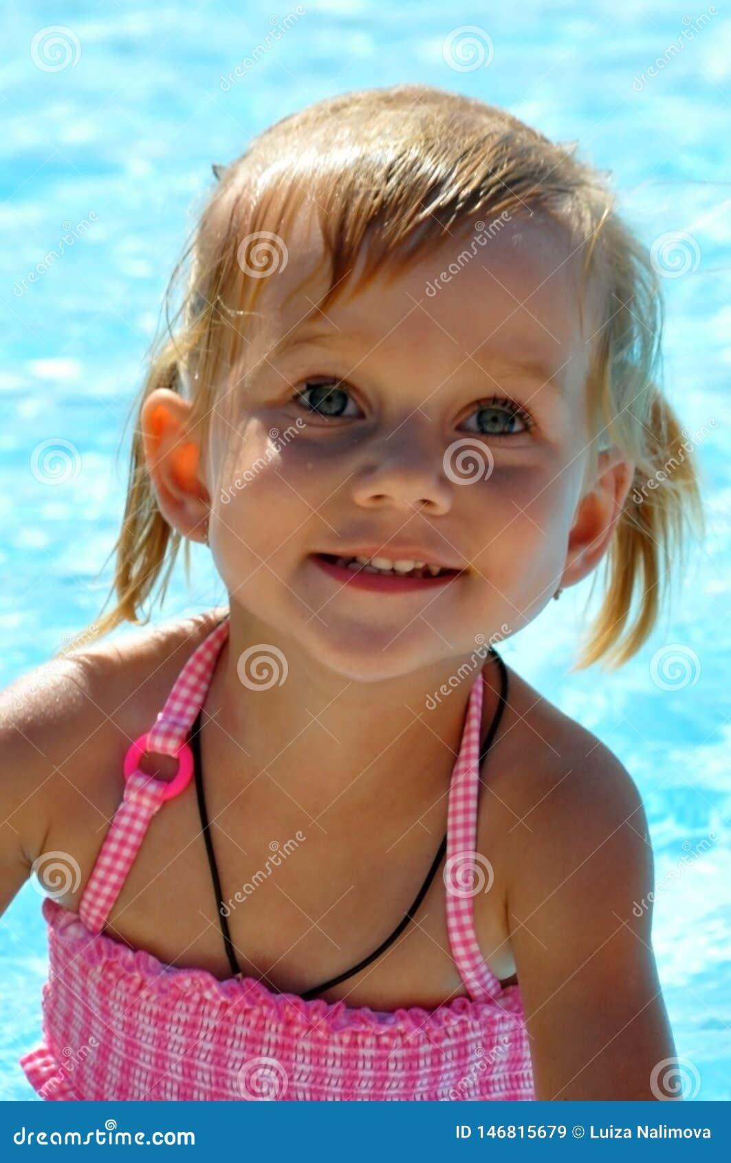 Härlig liten flicka med blåa ögon mot bakgrunden av pölen