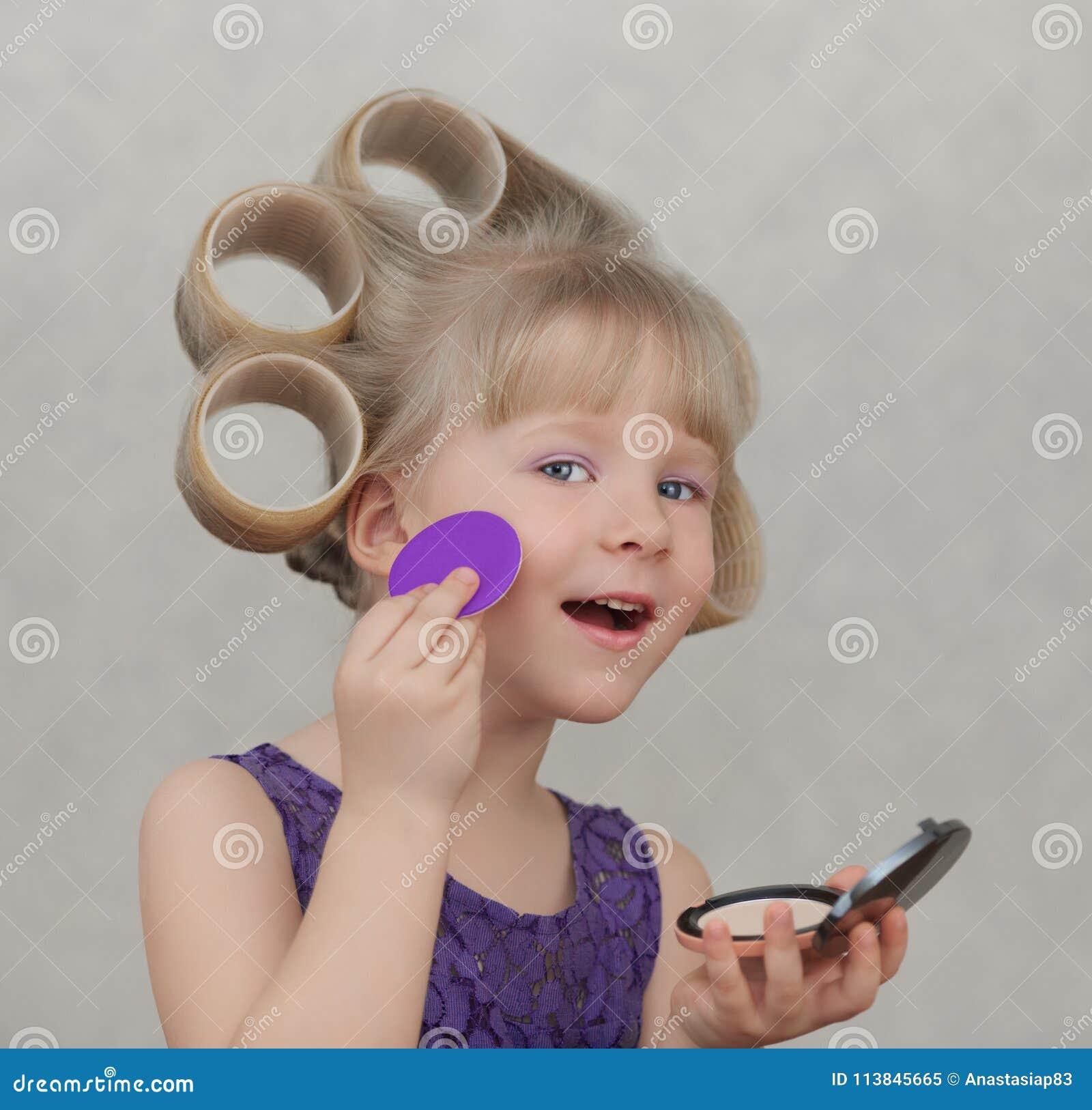 Härlig liten flicka som applicerar smink