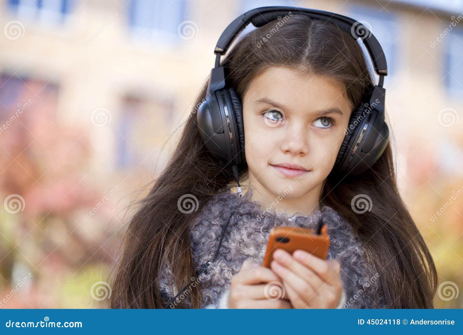 Härlig liten flicka som lyssnar till musik på hörlurar