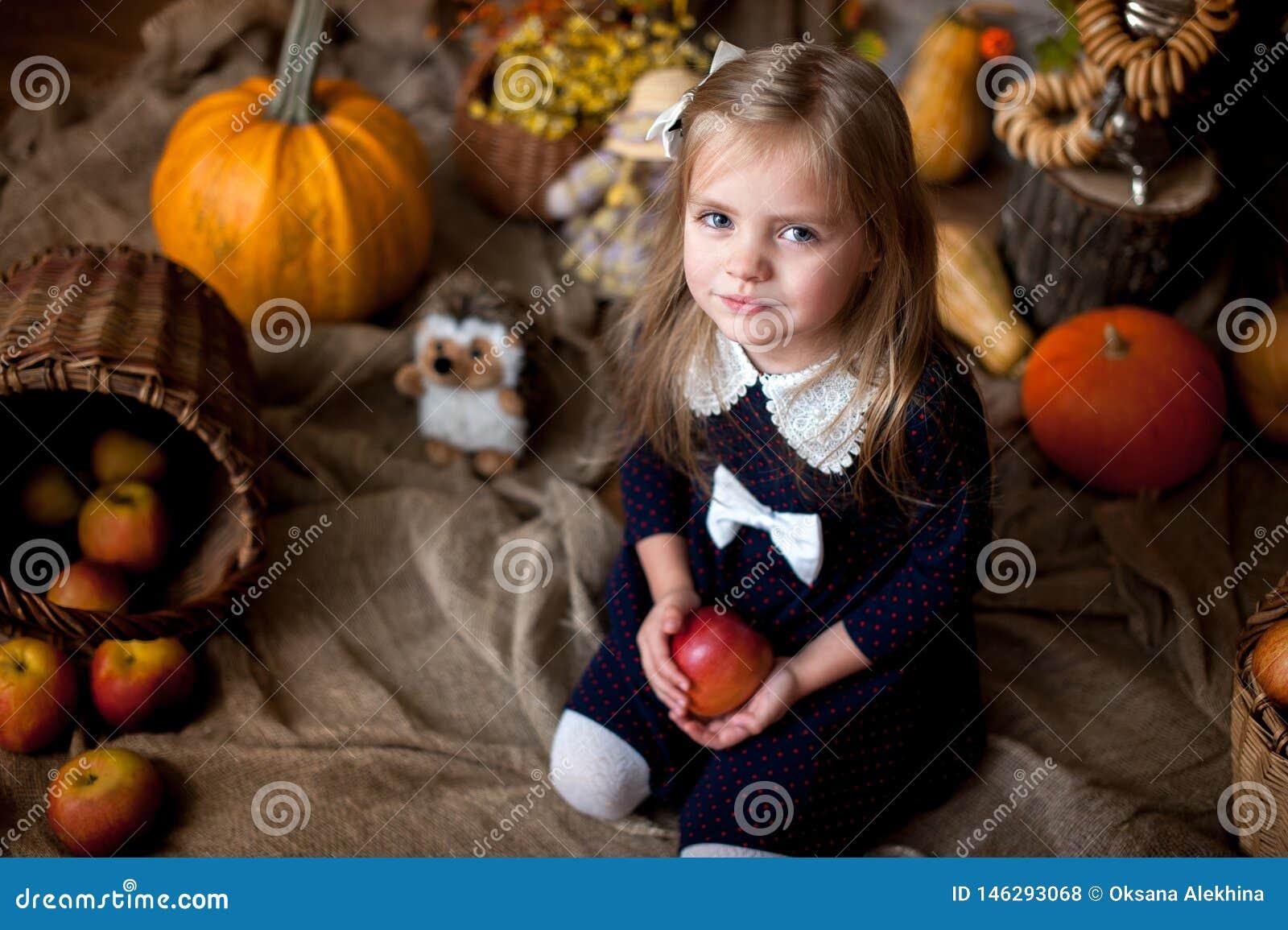 Härlig liten flicka som rymmer ett äpple