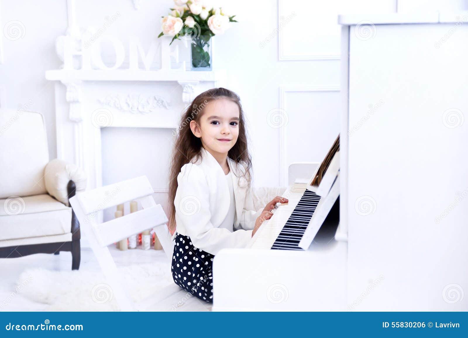 Härlig liten flicka som spelar pianot i vit vardagsrum