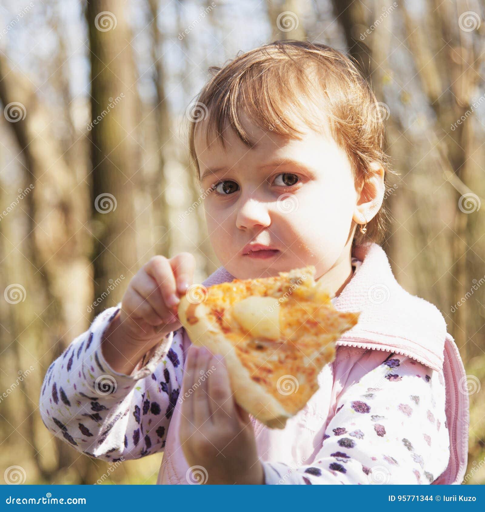 Härlig liten flicka som tycker om en läcker pizza i naturmat