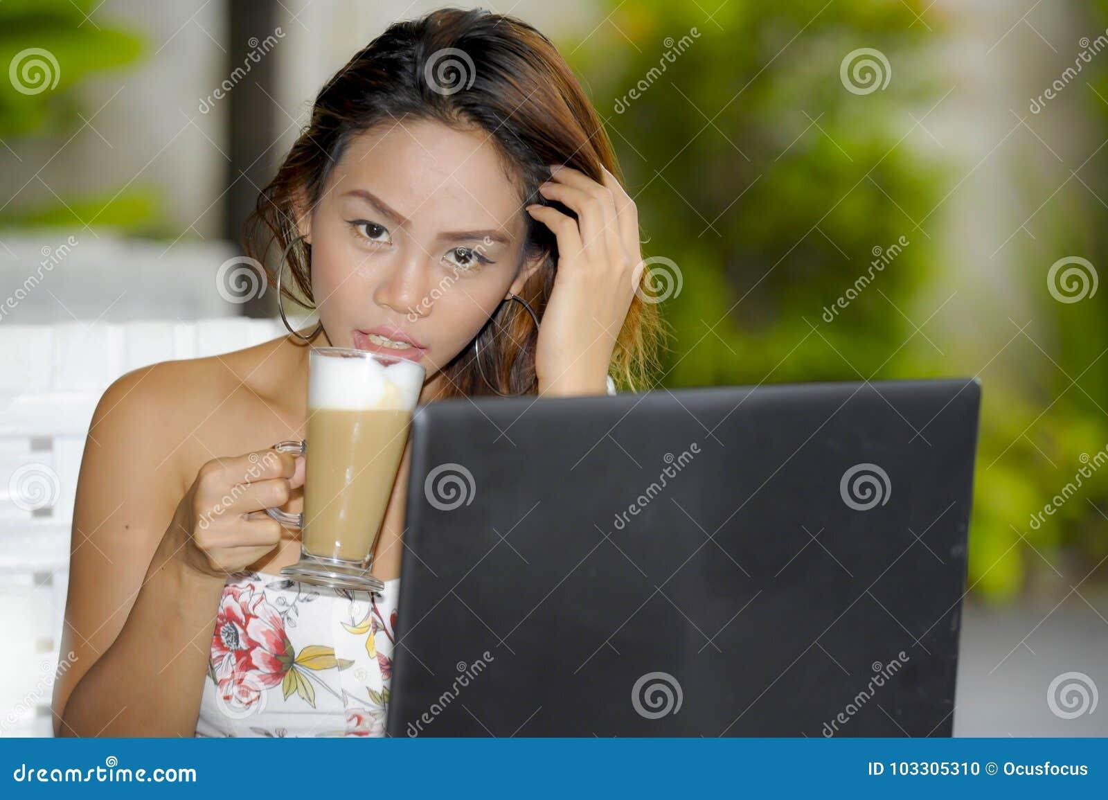 Härlig lycklig kvinna i sommarklänning utomhus på den trevliga coffee shop som har frukostnätverkande eller arbete med bärbar dat