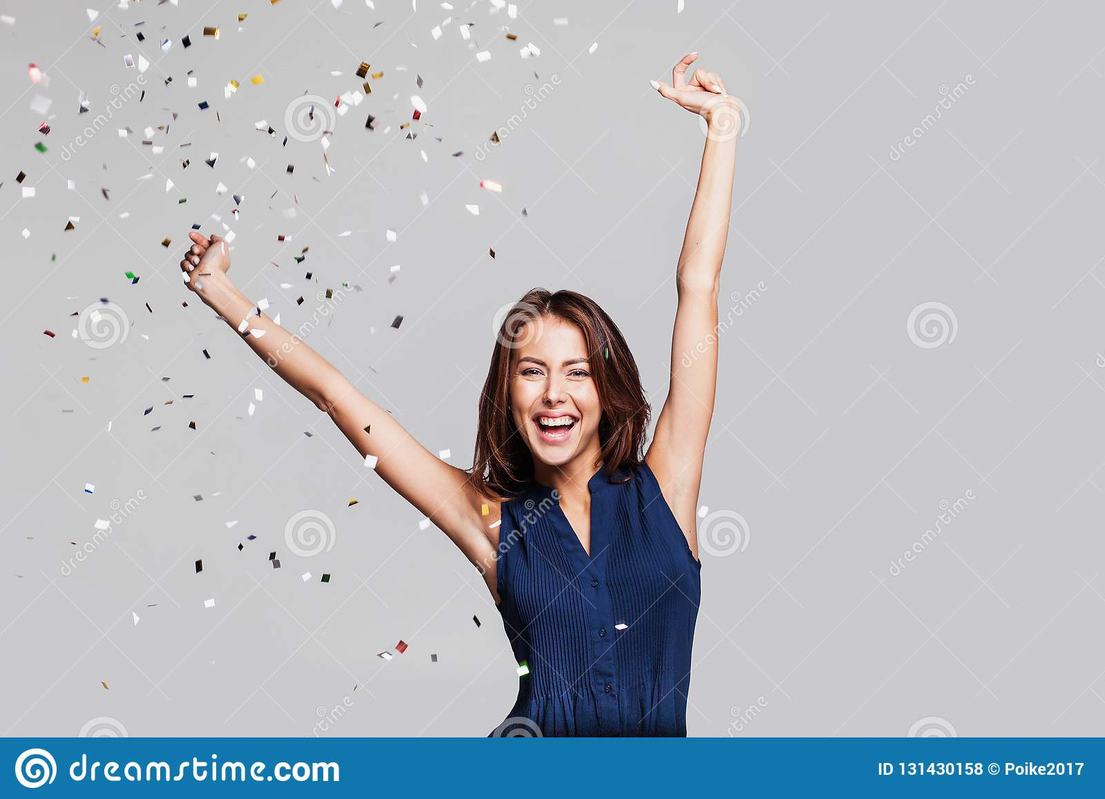 Härlig lycklig kvinna på berömpartiet med konfettier som överallt faller på henne Helgdagsafton för födelsedag som eller för nytt