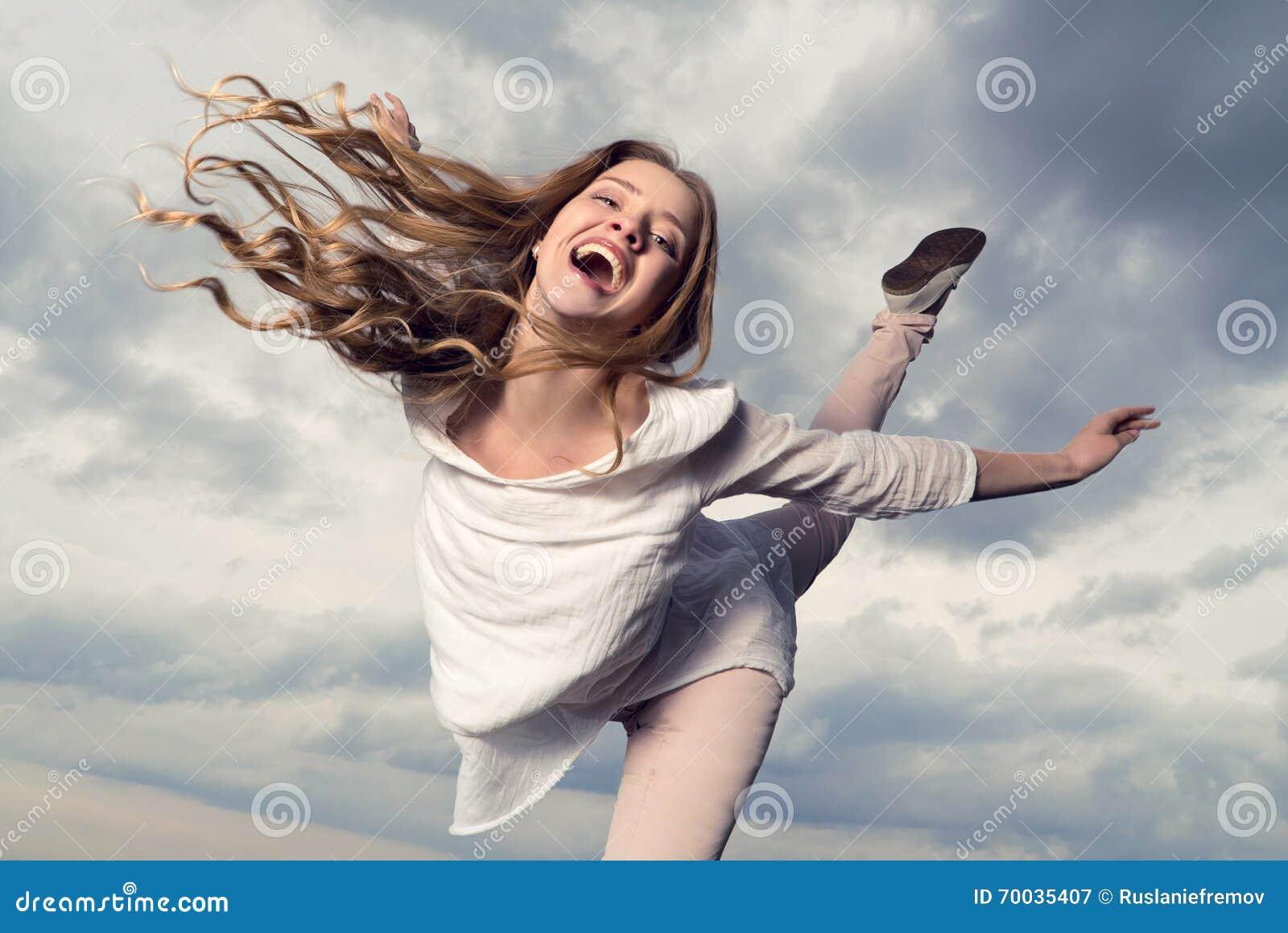 Härlig lycklig le kvinna med hårflyg i himmelbakgrunden