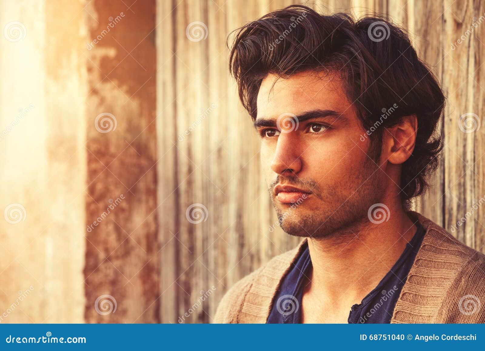 Härlig manslutstående Ung och stilig italiensk man med stilfullt hår