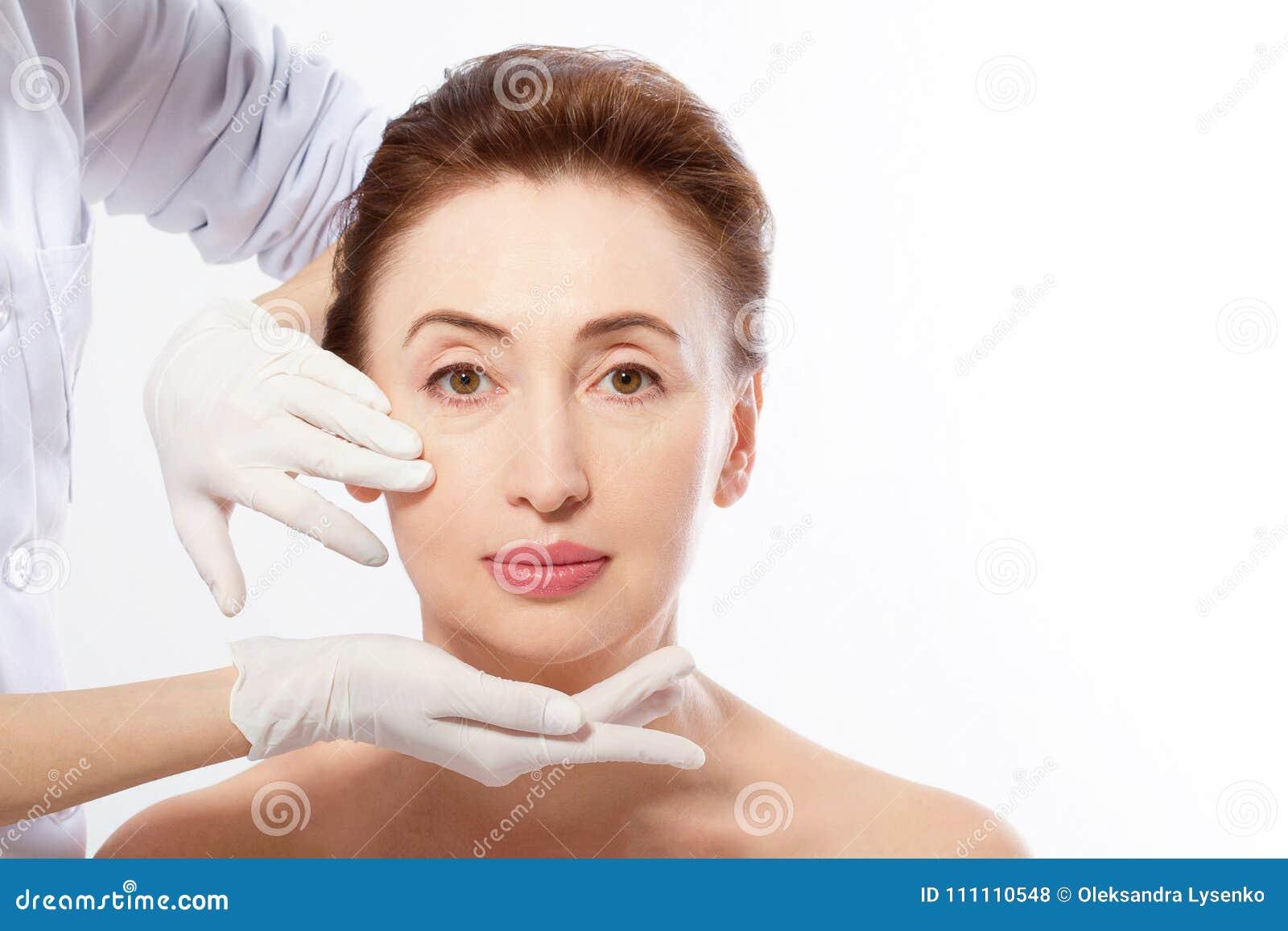 Härlig mellersta ålderkvinna för plastikkirurgi Makroframsida med händer för skrynkla- och doktors` som s isoleras på vit bakgrun