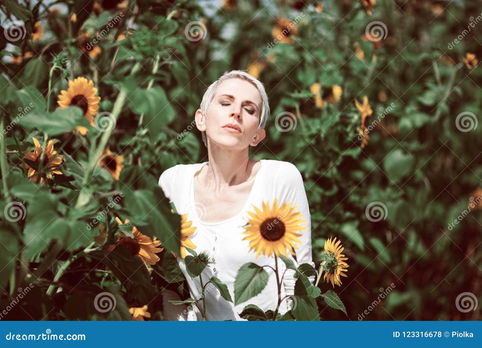 Härlig mellersta ålderkvinna i en lantlig fältplats utomhus med solrosor