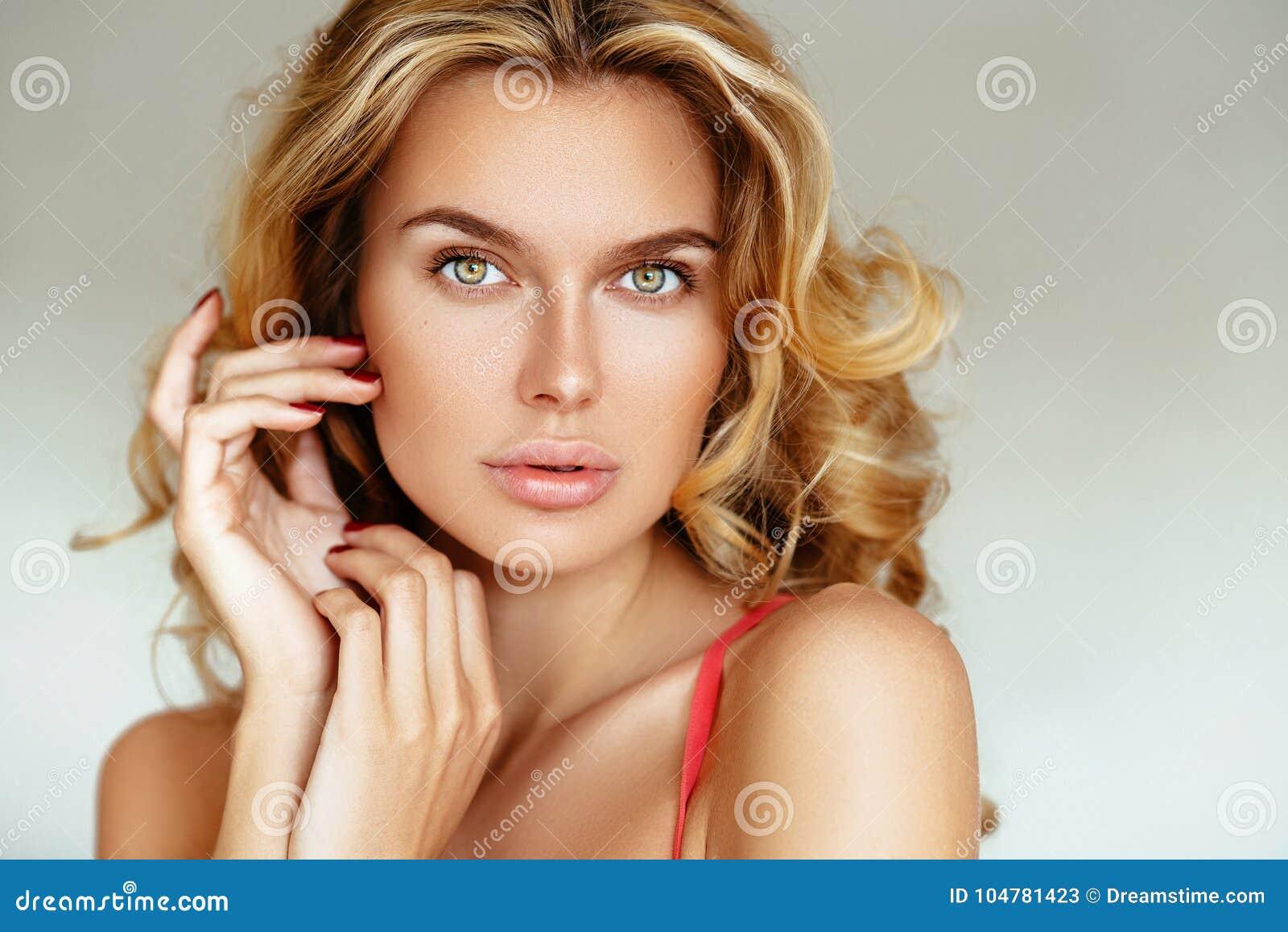 Härlig, mjuk sexig blond flicka med långt hår och pösiga kanter utan makeup som poserar i rosa damunderkläder på en vit bakgrund