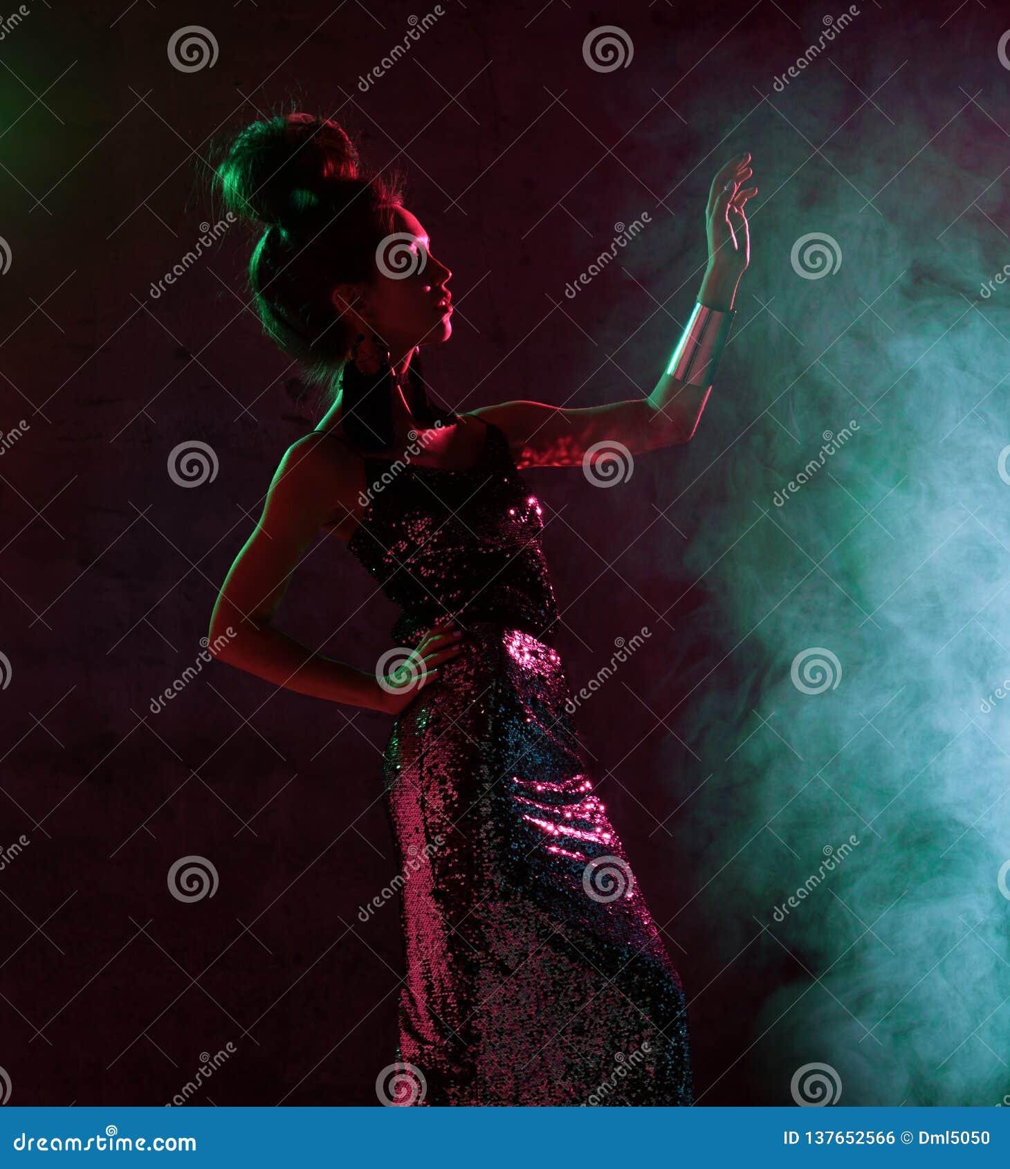 Härlig modebrunettkvinna som poserar i blått och rosa neonljus i guld- gnistrandeklänning för mode på mörker