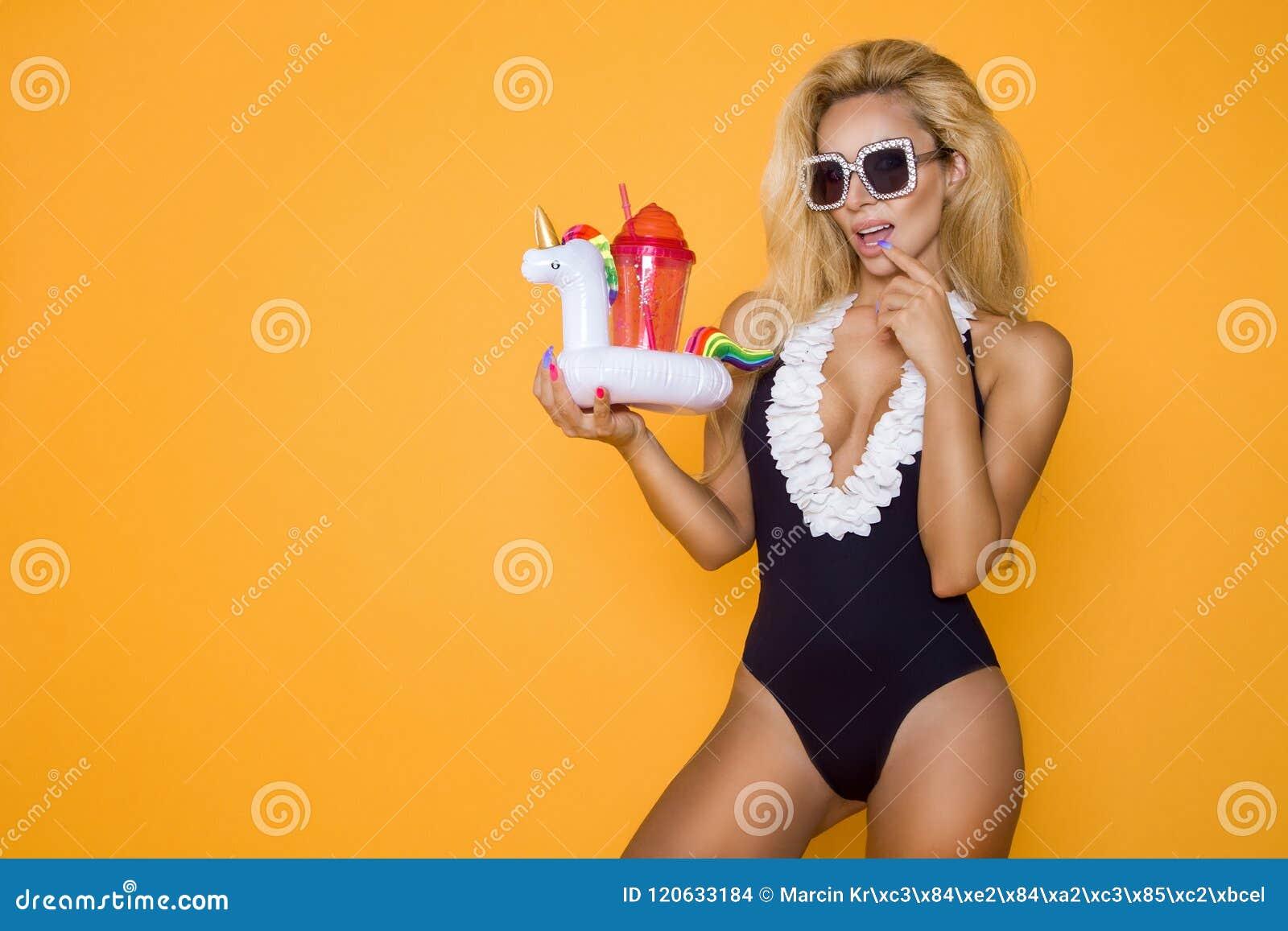 Härlig modell i en bikini och solglasögon och att rymma en drink och en uppblåsbar enhörning