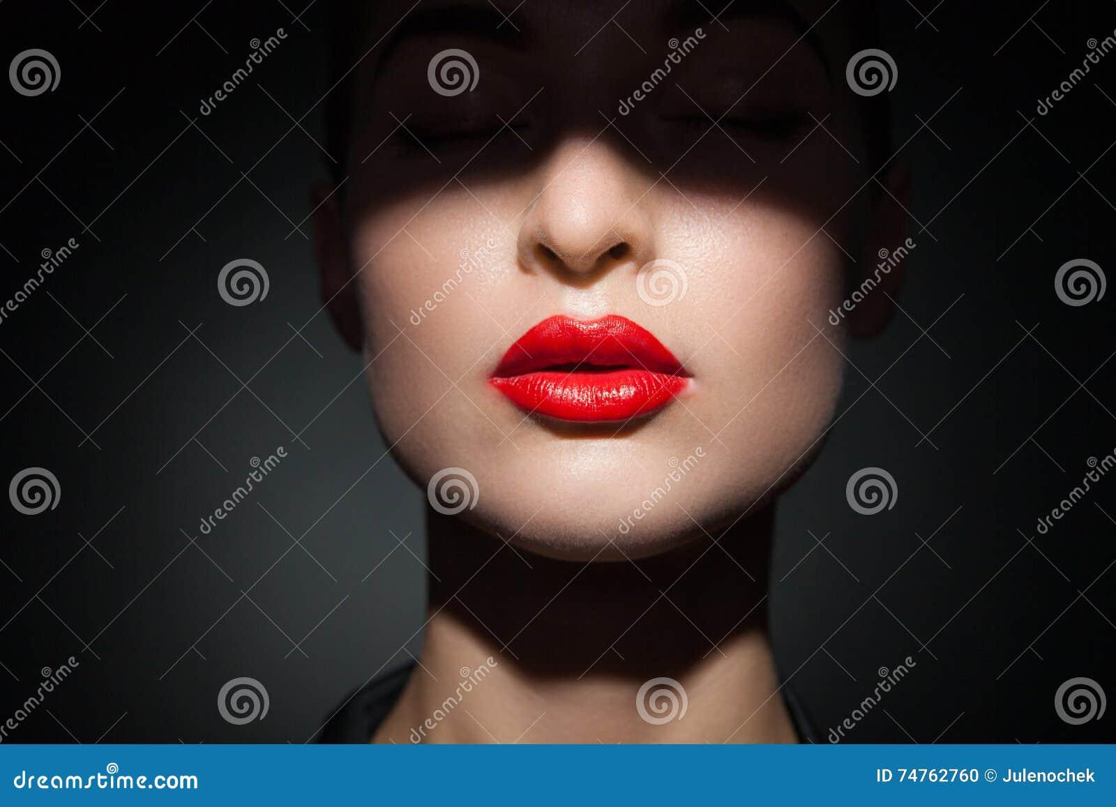Härlig modell med ljusa röda kanter och framsidahalvan som täckas i skugga