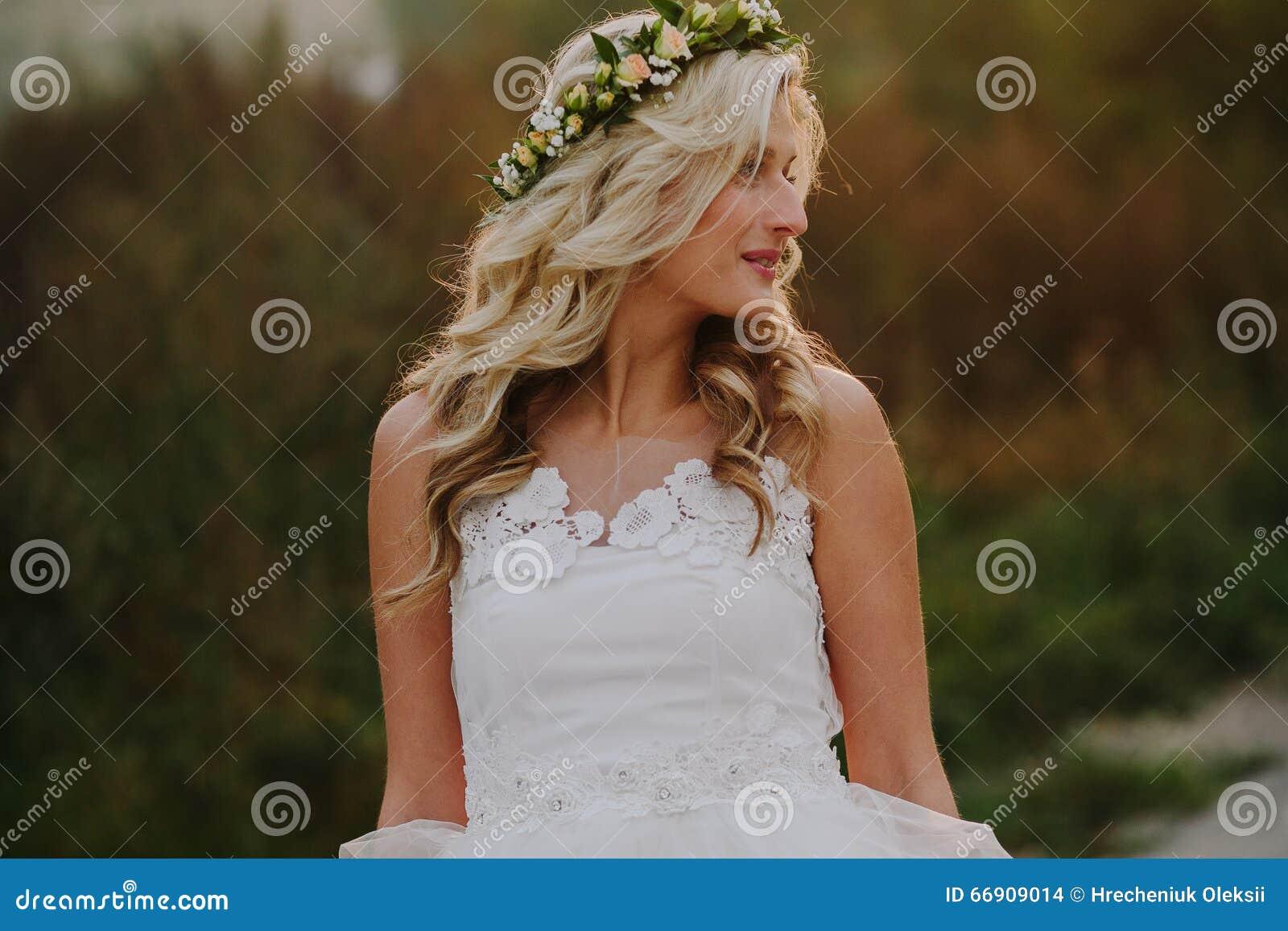 Härlig modellflicka i en vit bröllopsklänning