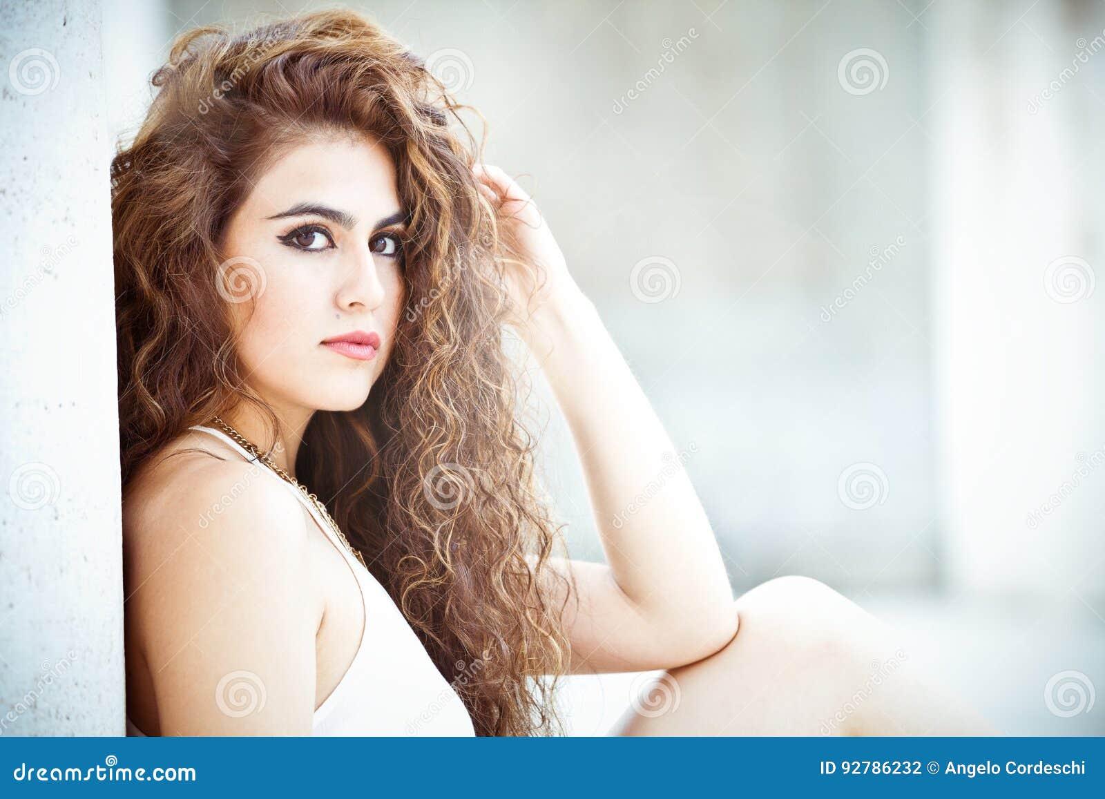 Härlig och attraktiv ung kvinna, långt lockigt hår
