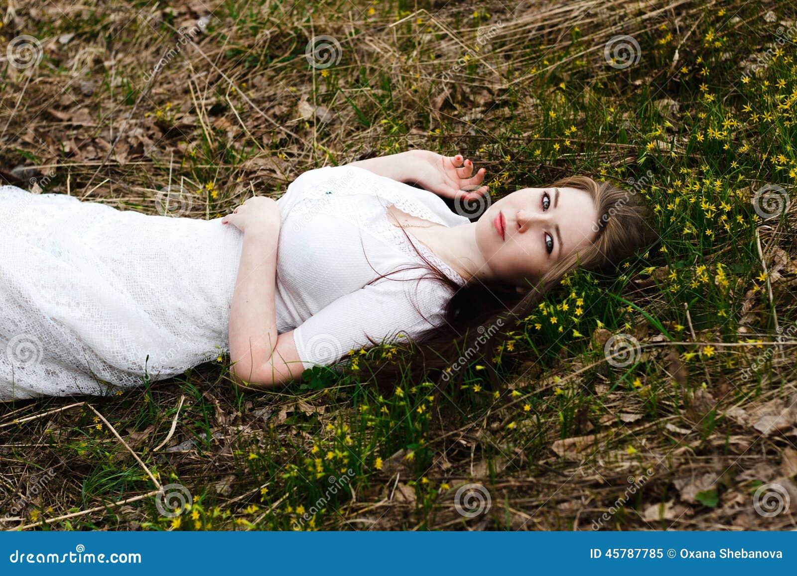 Härlig oskyldig kvinna i den vita klänningen som ligger på gräset