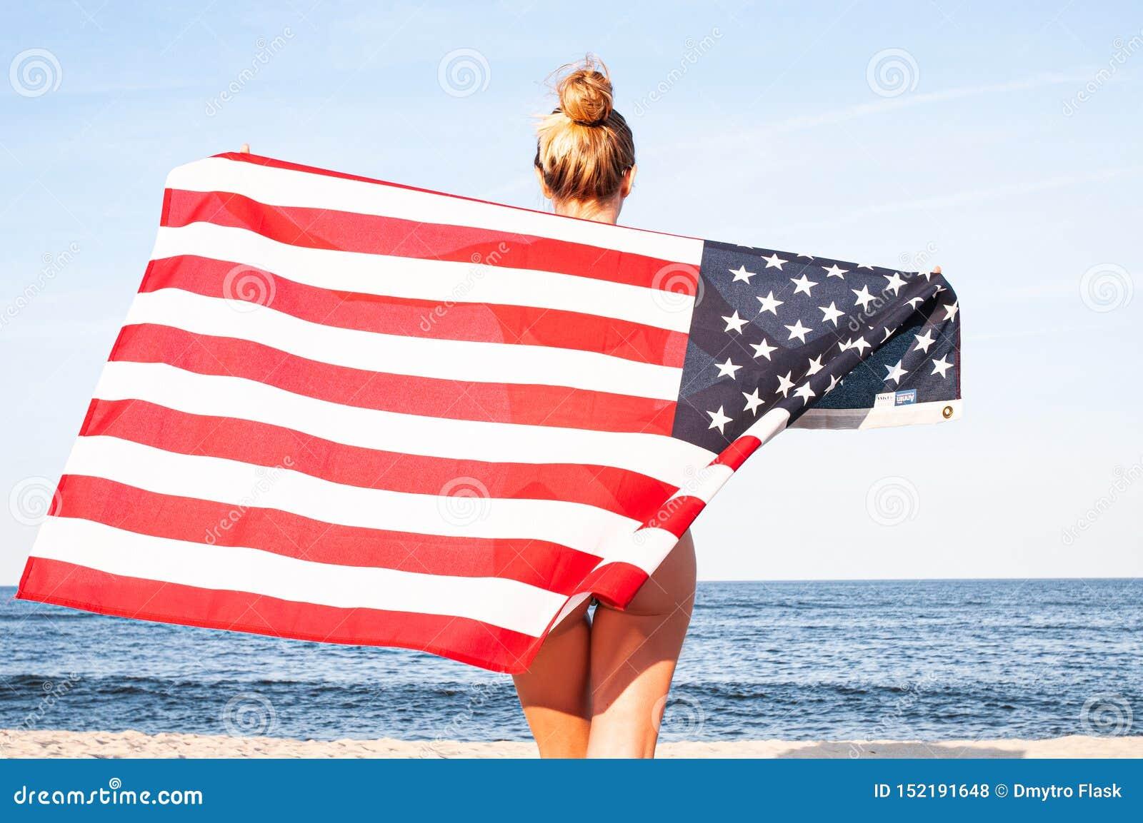Härlig patriotisk kvinna som rymmer en amerikanska flaggan på stranden USA självständighetsdagen, 4th Juli svart isolerad begrepp
