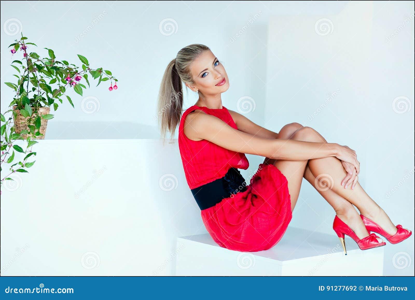Härlig sexig blond flicka med blåa ögon i ett rött klänningsammanträde