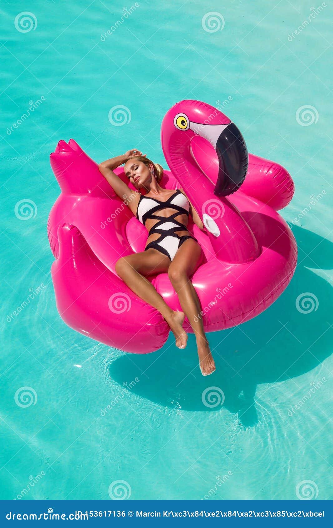 Härlig sexig fantastisk ung kvinna i en simbassäng som sitter på ett uppblåsbart rosa flammande och skrattar, brunbränd kropp, lå