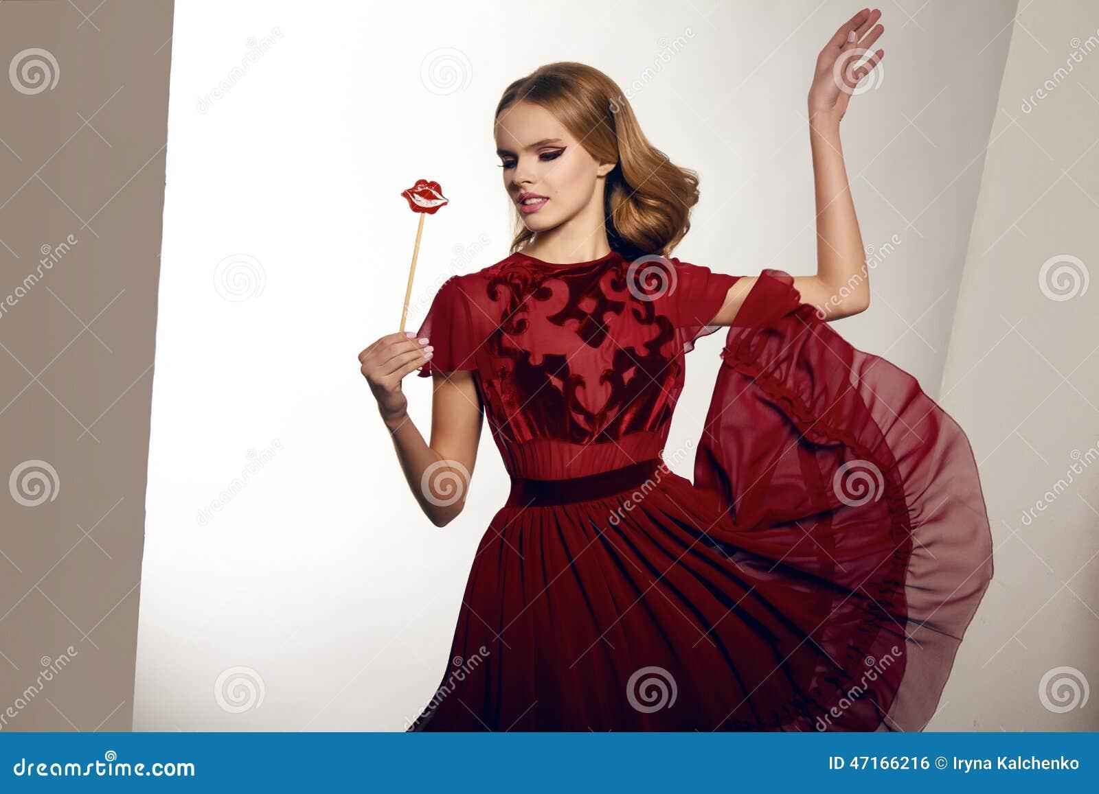 fb26e2e02ca6 Den härliga sexiga unga kvinnan med krabbt blont hår och det mjuka  naturliga sminket i bordovrmaftonkappa av chiffong och silke broderade med  att rymma en ...