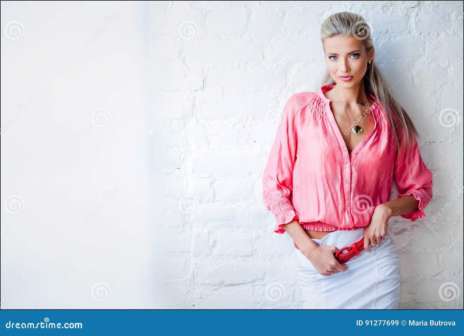 Härlig sexig sinnlig blond flicka i det rosa omslaget i Stuen