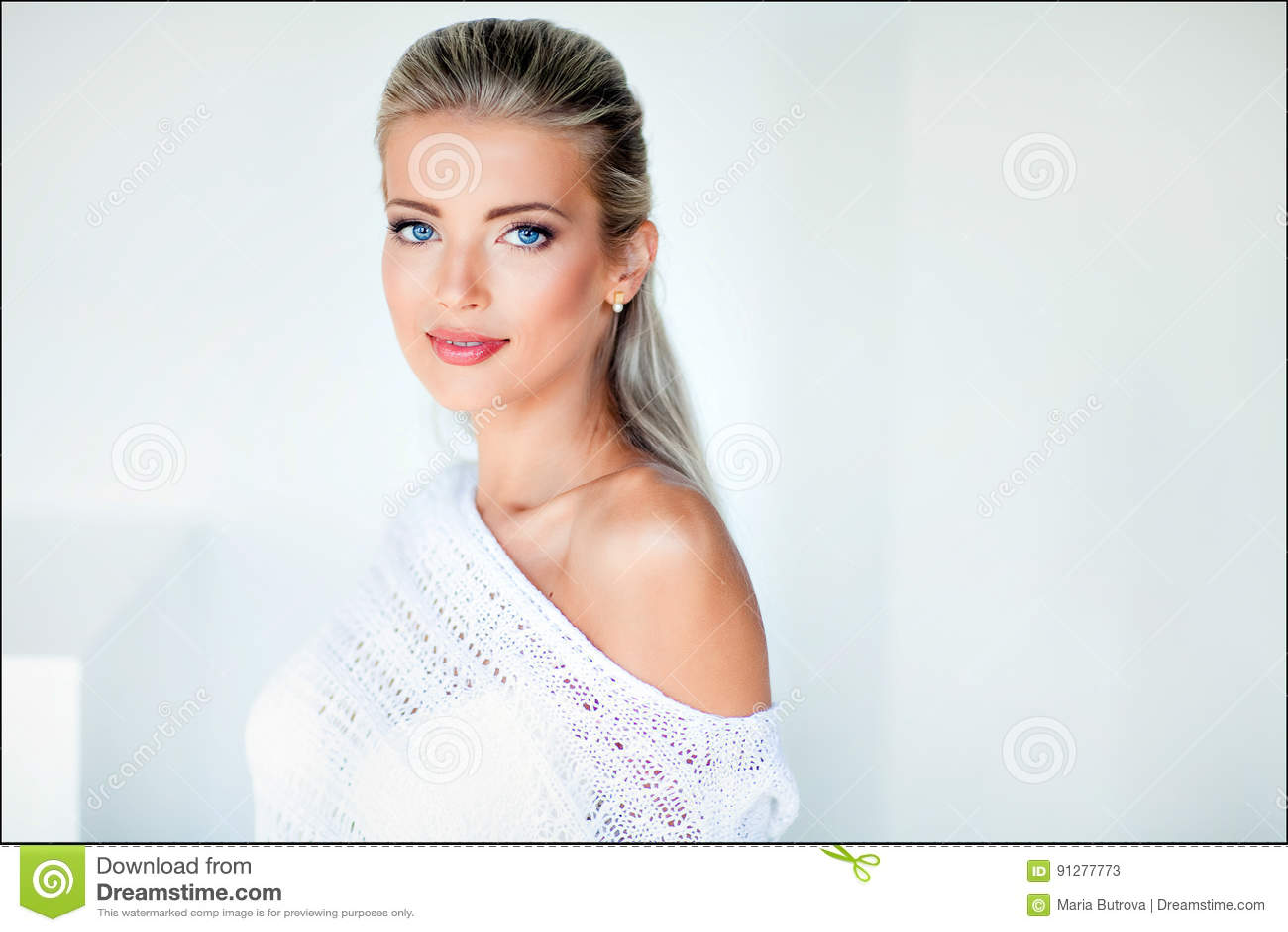 Härlig sexig sinnlig blond flicka i ett vitt omslag, studio