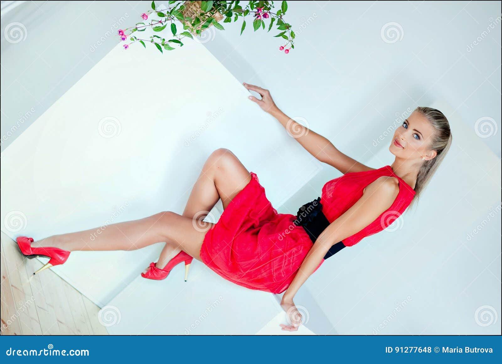 Härlig sexig sinnlig blond flicka med blåa ögon i en röd klänning